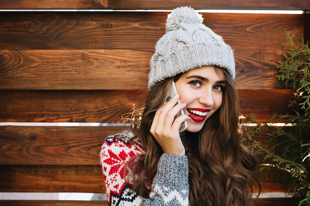 Closeup retrato linda garota com cabelo comprido e lábios vermelhos com chapéu de malha na madeira. ela usa um suéter quente, fala ao telefone, sorri.