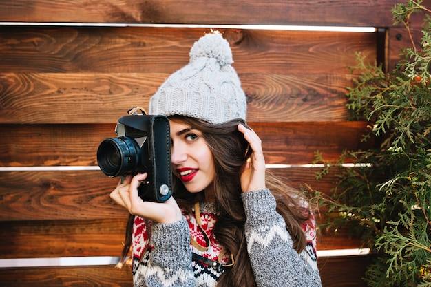 Closeup retrato linda menina morena com chapéu de malha e blusa quente, fazendo uma foto na câmera na madeira. ela está sorrindo.