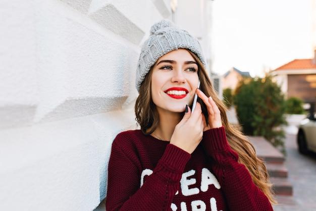 Closeup retrato linda morena com cabelos longos, com chapéu de malha e suéter marsala falando no telefone na rua. ela está sorrindo para o lado.