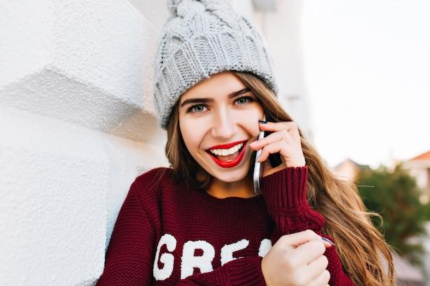 Closeup retrato linda morena com cabelos longos, com chapéu de malha e suéter marsala falando no telefone na rua. ela parece animada.