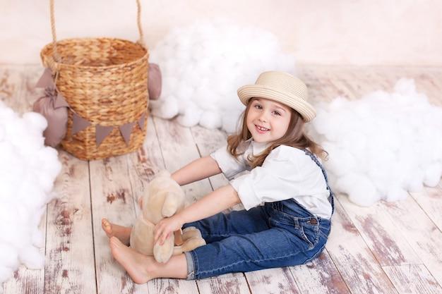 Closeup retrato sorridente menina de chapéu abraça um ursinho de pelúcia. criança brinca no quarto das crianças com um brinquedo.
