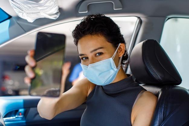 Closeup retrato tiro de mulher usando máscara facial, sentado no carro na unidade através da linha de vacinação contra o coronavírus, segurando o telefone móvel de tela preta em branco para o espaço da cópia no primeiro plano desfocado.