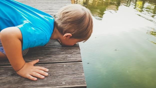 Closeup retrato tonificado do adorável menino ajoelhado no rio e olhando para o strider de água flutuando na superfície do lago
