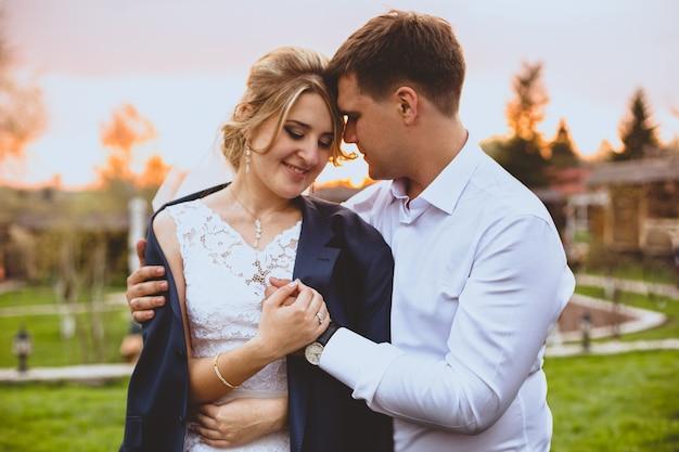 Closeup retrato tonificado do cuidadoso noivo abraçando a noiva no parque ao pôr do sol