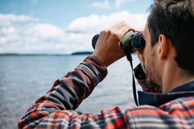 Closeup retrato traseiro de homem olhando através de binóculos