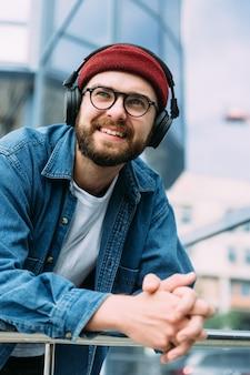 Closeup retrato vertical de feliz alegre barbudo hipster masculino bonito curtindo música em fones de ouvido na cidade. cena urbana.