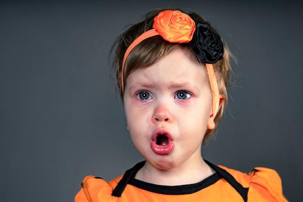 Closeup rosto de uma emoção infantil triste por crianças chorando em lágrimas no estúdio em um fundo preto ...