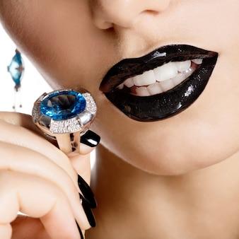 Closeup rosto de uma jovem mulher bonita com manicure preta e maquiagem brilhante de moda