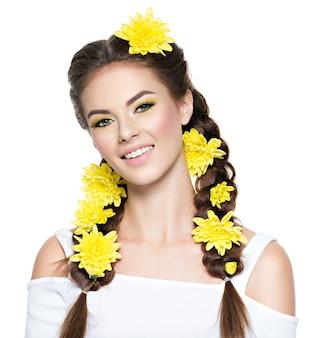 Closeup rosto de uma jovem mulher bonita e sorridente com maquiagem amarela brilhante retrato da moda garota atraente com rabo de cavalo elegante penteado isolado no branco.
