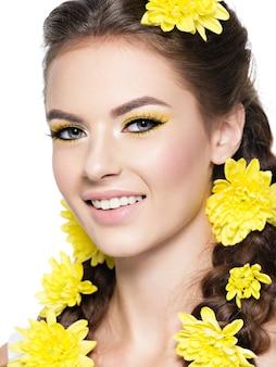 Closeup rosto de uma jovem sorridente e bonita com maquiagem amarela brilhante. retrato da moda