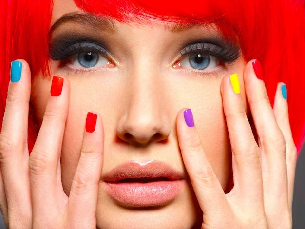 Closeup rosto de uma linda garota com unhas brilhantes e multicoloridas.
