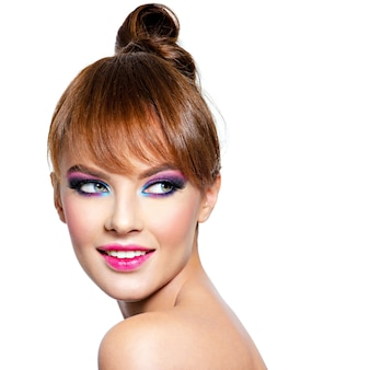 Closeup rosto de uma linda mulher com maquiagem brilhante e vívida modelo com maquiagem criativa nos olhos isolada no branco menina com cabelo ruivo mulher sorrindo, olhando para longe