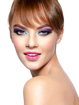 Closeup rosto de uma linda mulher com maquiagem brilhante e vívida. modelo com maquiagem criativa nos olhos - isolada no branco. menina com cabelo ruivo. penteado curto com franja