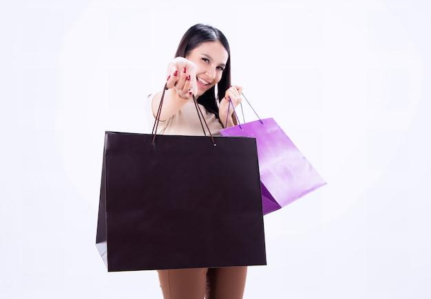 Closeup sacola de compras estava mostrando pela mão da mulher de beleza turva, com sorriso e cara feliz, shopaholic