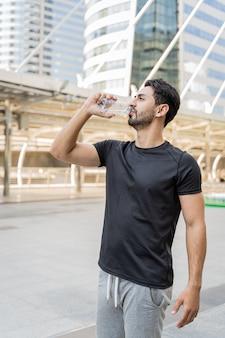Closeup saúde esporte homem beber água de uma garrafa depois de correr na cidade