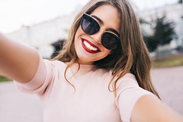 Closeup selfie-retrato de garota atraente em óculos de sol com penteado longo e sorriso branco como a neve na cidade.