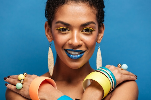 Closeup sensual mulata nua com maquiagem moda e acessórios posando na câmera com as mãos cruzadas sobre os ombros, sobre azul
