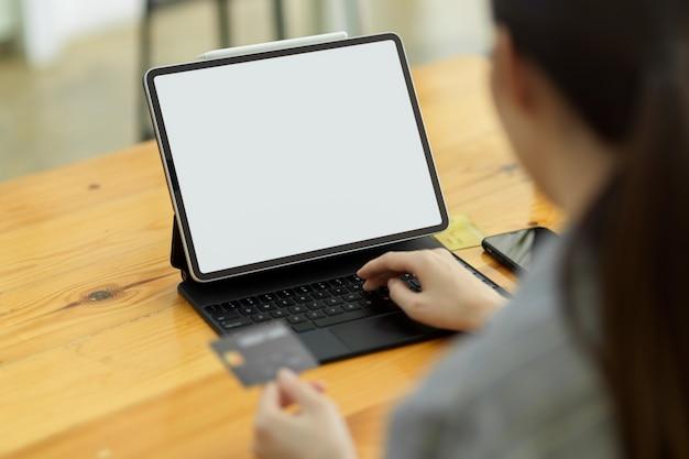 Closeup, simulação de imagem de tablet digital portátil com teclado, fêmea digitando no teclado segurando cartão de crédito, aplicativo, compras online, conceito de transferência de dinheiro