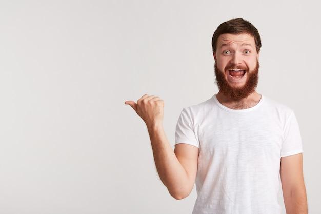 Closeup sorridente jovem atraente hippie com barba usa camiseta e se sente feliz e aponta para o lado para copyspace com o dedo isolado sobre a parede branca