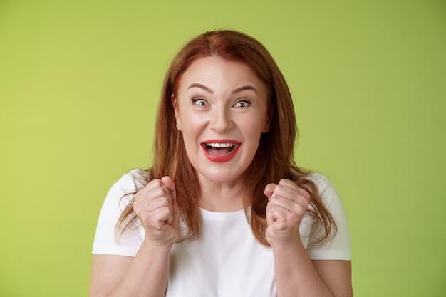 Closeup sortudo entusiástico ruivo fofo alegre mulher de meia idade levantando os punhos vigoroso entusiasmo comemorando sorrindo amplamente vencendo comemorando triunfando sucesso boas notícias