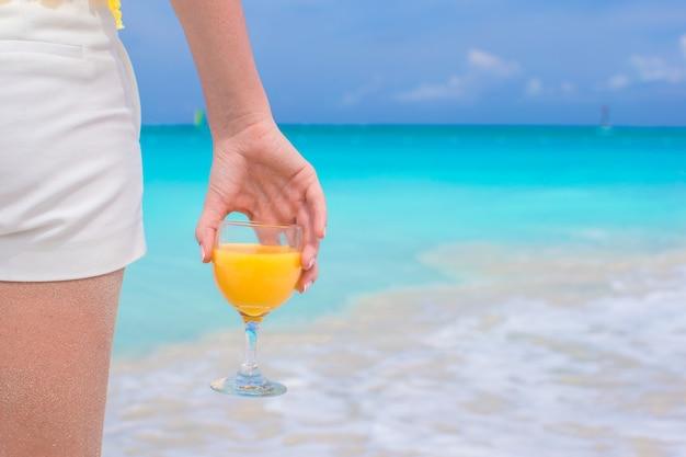 Closeup suco de laranja em uma mão feminina no fundo do mar