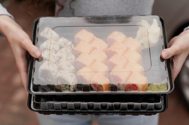Closeup sushi no serviço online de entrega de comida saudável de caixa. menina tem 2 conjuntos de sushi nas mãos. rolinhos da culinária japonesa, molho de soja, wasabi.