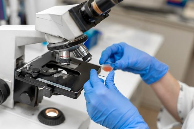 Closeup técnico de laboratório pesquisa amostra de sangue no microscópio.