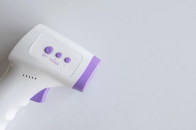 Closeup termômetro infravermelho no fundo da mesa branca