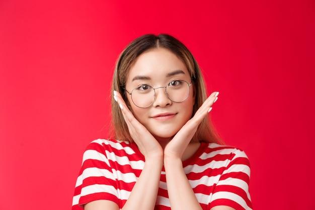 Closeup terna linda garota asiática adolescente finalmente se livrou das espinhas, falhas na pele, toque em aplicação de pele limpa e pura.