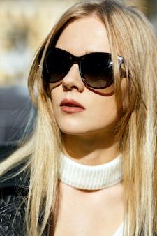 Closeup tiro da fabulosa modelo loira com cabelo comprido, vestindo jaqueta de couro e óculos escuros