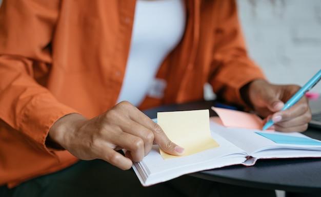 Closeup tiro da mão do aluno, segurando a caneta, lembrete no quadro de planejamento, preparação para o exame, ensino à distância
