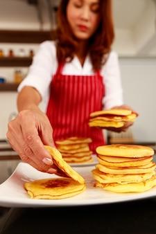 Closeup tiro da pilha de lanche de panqueca recém-assado gostoso fofo quente dourado bom cheiro na mão do chef que usa avental vermelho enquanto pega o pão da pilha em primeiro plano desfocado.