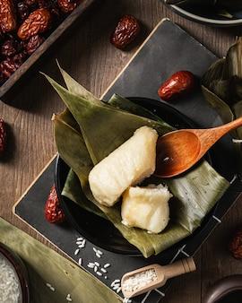 Closeup tiro da preparação de bolinho de arroz com folhas de bananeira
