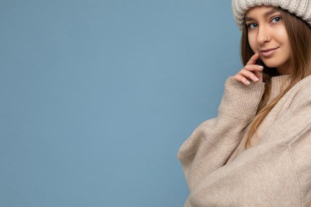 Closeup tiro de atraente feliz sexy jovem loira escura em pé, isolado na parede de fundo azul, vestindo um suéter bege quente e um chapéu bege de inverno, olhando para a câmera e sonhando