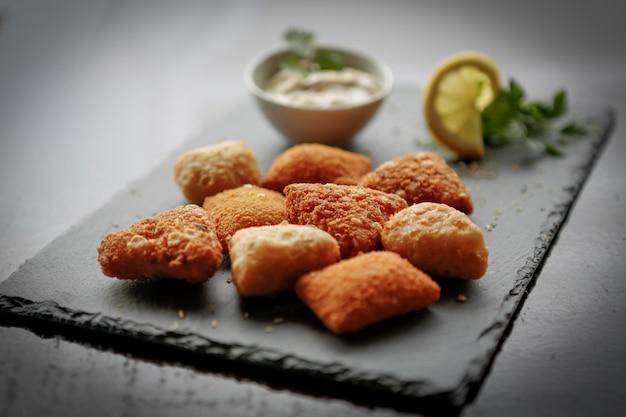 Closeup tiro de bolinhos de batata frita com queijo ou croquetes sobre um tabuleiro de pedra escura