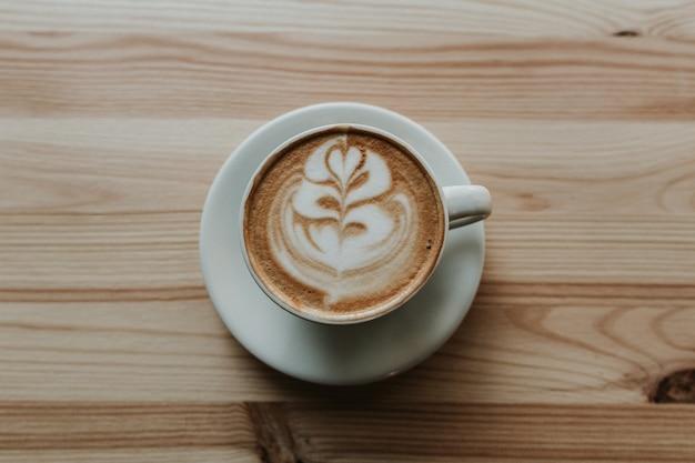 Closeup tiro de café com latte art na xícara de chá de cerâmica branca em uma mesa de madeira
