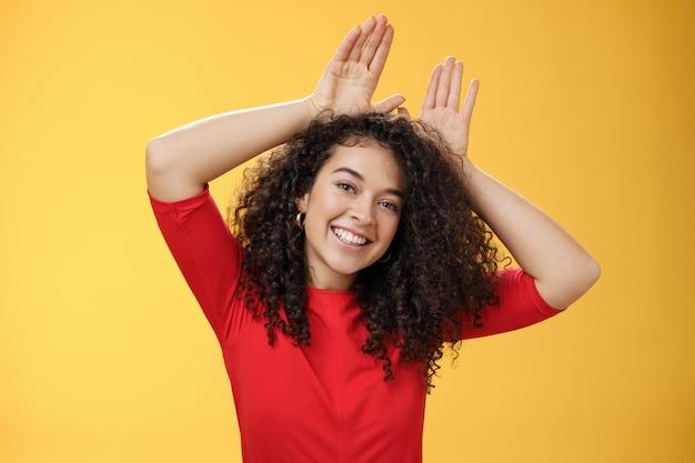 Closeup tiro de carismática lúdica e tenra jovem tipo mulher com cabelo encaracolado, jogando se divertindo ...