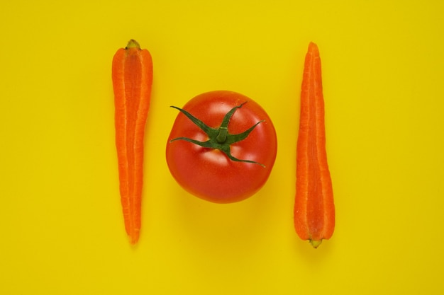 Closeup tiro de cenoura e tomate isolado em amarelo.