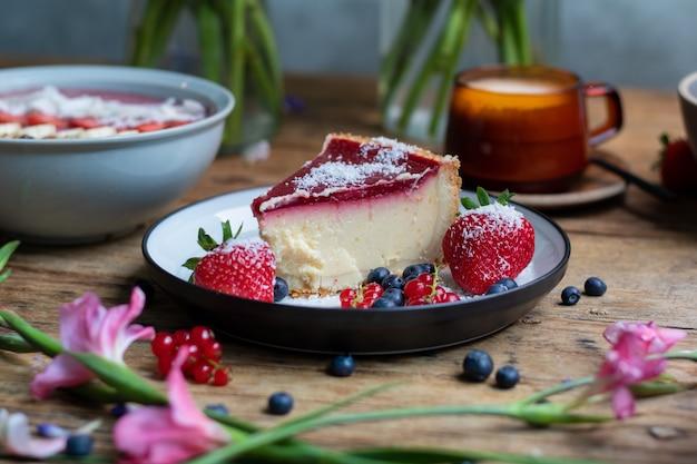 Closeup tiro de cheesecake com geleia decorada com morangos e frutas vermelhas