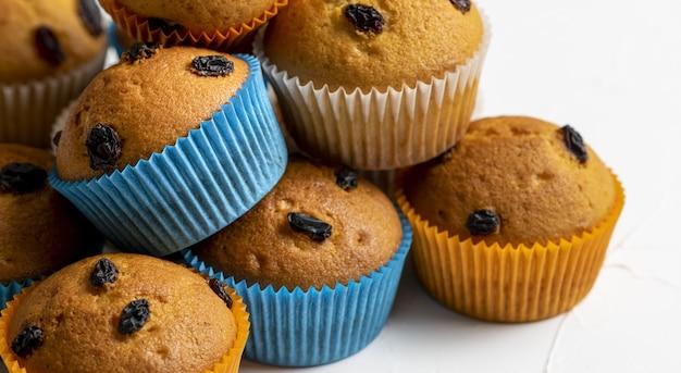 Closeup tiro de cupcakes com papéis laranja e azuis em um fundo branco