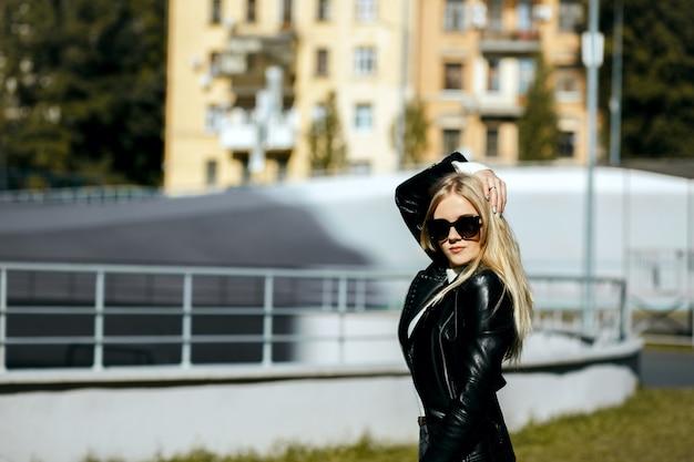 Closeup tiro de deslumbrante mulher loira com cabelo comprido, vestindo jaqueta de couro e óculos escuros. espaço para texto