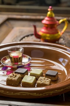 Closeup tiro de diferentes tipos de doces em forma de quadrado com chá em uma bandeja de madeira
