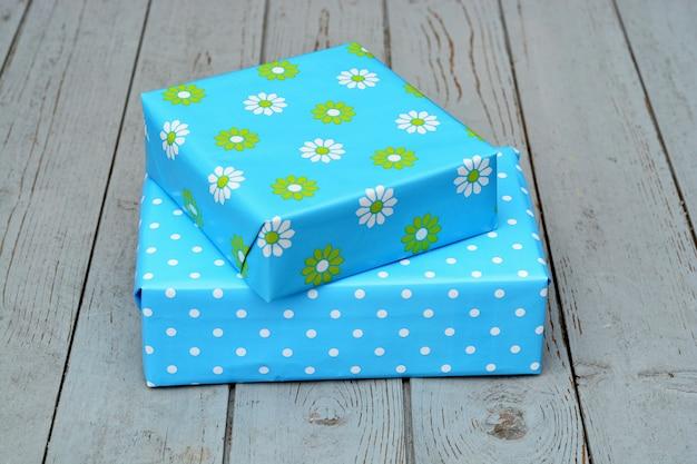 Closeup tiro de duas caixas de presente em um embrulho azul empilhadas uma em cima da outra em uma superfície de madeira