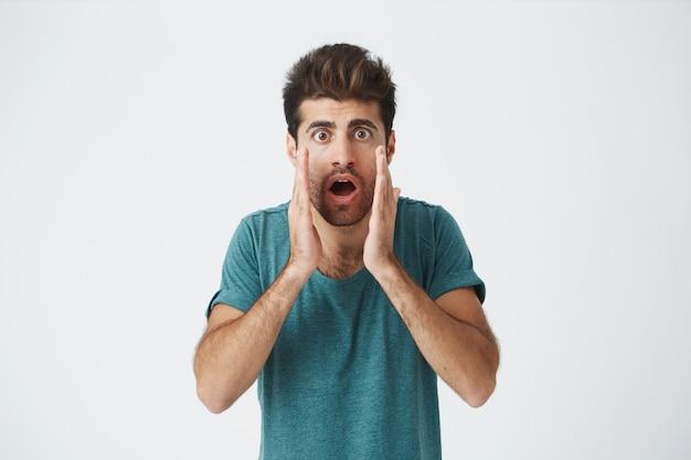 Closeup tiro de elegante jovem espanhol hipster em camiseta azul, com expressão nervosa, gritando e aplaudindo seu time de futebol favorito que vai perder partida.