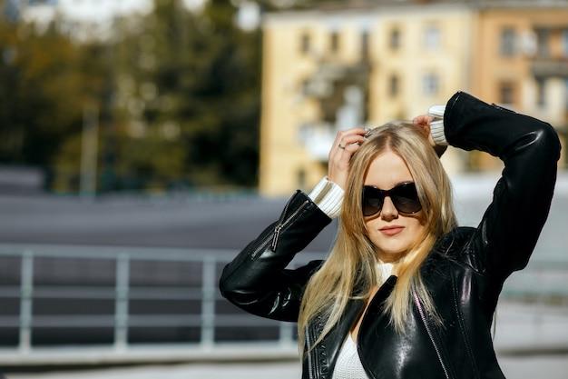 Closeup tiro de elegante mulher loira vestindo jaqueta de couro preta e óculos escuros. espaço para texto