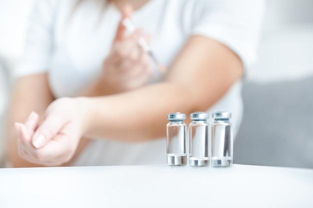 Closeup tiro de frascos de vidro com insulina contra mulher fazendo picada
