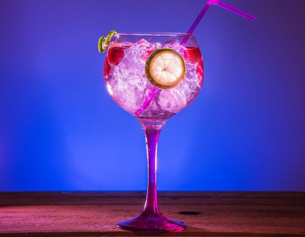 Closeup tiro de gin tônica rosa com framboesas e limão