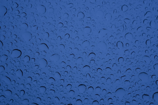 Closeup tiro de gotas grandes e pequenas de água no vidro azul - perfeito para o fundo