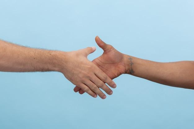 Closeup tiro de humano de mãos dadas isolado em azul