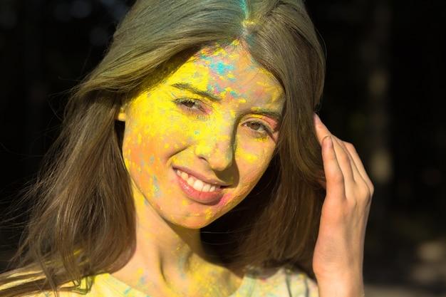 Closeup tiro de jovem atraente posando com pó de holi no rosto e pescoço